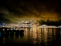 Port of Seattle at night with clouds lit by warm industrial light in Elliot Bay Washington state, USA