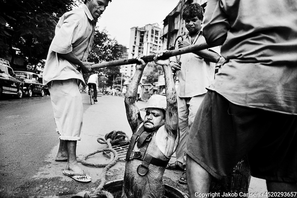 A worker is lowered into the sewer in Mumbai, India, to clean it with his bare hands.