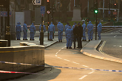 Westminster, London, March 23rd 2017. With Westminster Bridge, scene of Wednesday's terror attack reopened following forensic investigations, members of the public lay flowers. Forensic investigations continue near the entrance to the Houses of Parliament.