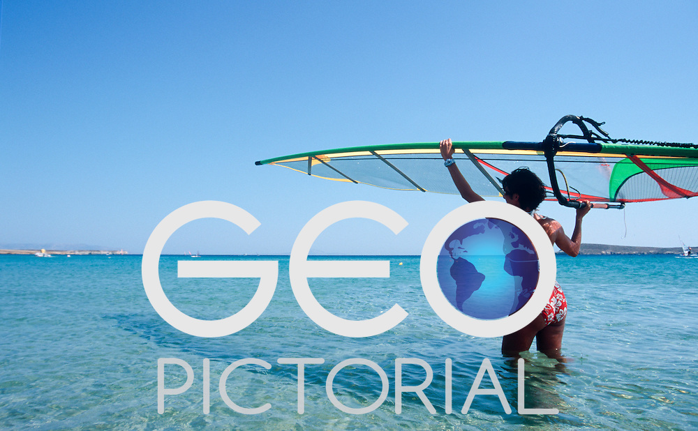 A girl carries a windsurf sail to the water at the Sunwind Surf Club, New Golden Beach, Paros, Cyclades Islands, Greece.