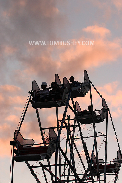 Middletown, N.Y. - People riding on a ferris wheel at a carnival are silhouetted against the clouds at twilight on May 20, 2006. ©Tom Bushey