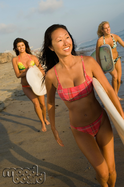 Surfers in Bikinis Walking Along Beach