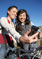 Two young women standing with bicycle photographing selves with digital camera.
