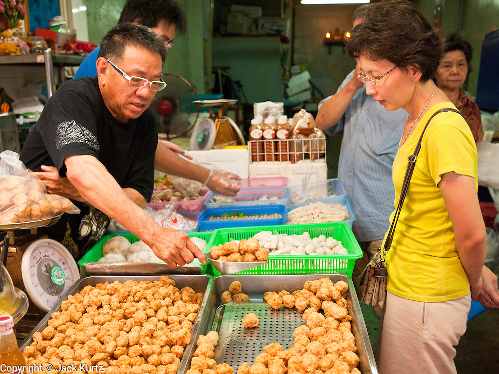 09 JULY 2011 - BANGKOK, THAILAND: A fried food vendor prepares a woman's order in the Chinatown section of Bangkok, Thailand. Chinatown is the entrepreneurial hub of Bangkok, with thousands of family owned businesses selling wholesale merchandise in everything from food like rice, peanuts and meats, to dry goods like toys and shoes.  PHOTO BY JACK KURTZ