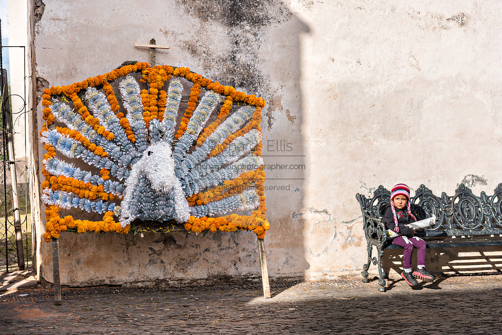 A young boy sits near an altar for the Day of the Dead festival October 31, 2017 in Tzintzuntzan, Michoacan, Mexico.