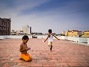 24 FEBRUARY 2015 - PHNOM PENH, CAMBODIA: Children play on the roof of the White Building. The White Building, the first modern apartment building in Phnom Penh, originally had 468 apartments, and was opened the early 1960s. The project was overseen by Vann Molyvann, the first Cambodian architect educated in France. The building was abandoned during the Khmer Rouge occupation. After the Khmer Rouge were expelled from Phnom Penh in 1979, artists and dancers moved into the White Building. Now about 2,500 people, mostly urban and working poor, live in the building. Ownership of the building is in dispute. No single entity owns the building, some units are owned by their occupants, others units are owned by companies who lease out apartments. Many of the original apartments have been subdivided since the building opened and serve as homes to two or three families. The building has not been renovated since the early 1970s and is in disrepair. Phnom Penh officials have tried to evict the tenants and demolish the building but residents refuse to move out.   PHOTO BY JACK KURTZ