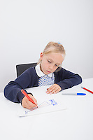 Little female student drawing on paper at table