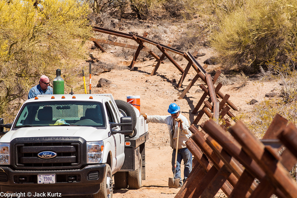 """03 MAY 2012 - VEKOL VALLEY, RURAL PINAL COUNTY, AZ:    Eric Reynolds (CQ LEFT) and James Peters (CQ) both from the BLM office in Safford, work on vehicle barriers on Bureau of Land Management land south of Interstate 8 and west of Casa Grande in rural Pinal County. The area has been a hotbed of illegal immigrant and drug smuggling for years. The BLM has undertaken a series of """"surges"""" in the area, increasing their law enforcement patrols and partnering with Border Patrol and Pinal County Sheriff's Department officers to reduce criminal activity in the area.       PHOTO BY JACK KURTZ"""
