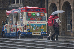 © licensed to London News Pictures. London, UK 24/06/2012. A couple walking past an ice-cream van under the rain in central London, today (24/06/12). Photo credit: Tolga Akmen/LNP