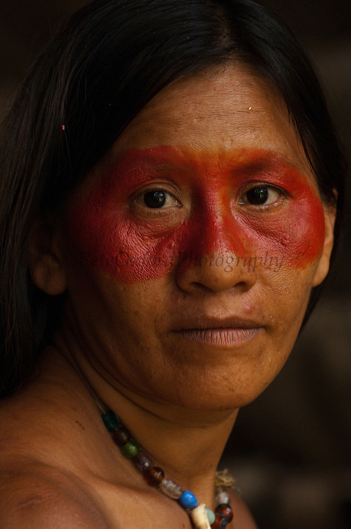 Huaorani Indian, Ewa Kemperi withbtraditional Huaorani mask face paint from the Achiote fruit.<br /> Bameno Community. Yasuni National Park.<br /> Amazon rainforest, ECUADOR.  South America<br /> This Indian tribe were basically uncontacted until 1956 when missionaries from the Summer Institute of Linguistics made contact with them. However there are still some groups from the tribe that remain uncontacted.  They are known as the Tagaeri &amp; Taromenane. Traditionally these Indians were very hostile and killed many people who tried to enter into their territory. Their territory is in the Yasuni National Park which is now also being exploited for oil.