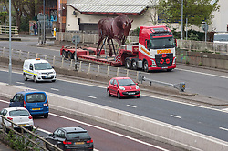 "© Licensed to London News Pictures. 23/04/2018. Bristol, UK. A five metre tall steel ""Warhorse"" sculpture leaves Bristol for a trip of 196 miles by road to West Yorkshire to be part of a war memorial. The horse has been crafted by Bristol sculpture company Codsteaks and weighs about two tonnes. The war memorial is heading to Featherstone to coincide with the 100th anniversary of the end of World War I. Photo credit: Simon Chapman/LNP"