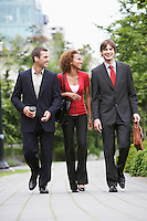 Two business men and woman walking through park