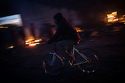 A migrant is seen passing by some fire in the Calais migrants camp, France. FEDERICO SCOPPA/CAPTA