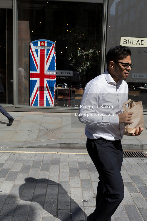 Lunchtime City workers walk past the Union Jack-themes telephone kiosk in celebrity chef Gordon Ramsey's restaurant Bread Street Kitchen on (the former Roman thoroughfare) Watling Street, in the City of London, the capital's financial district (aka the Square Mile), on 22nd August 2019, in London, England.