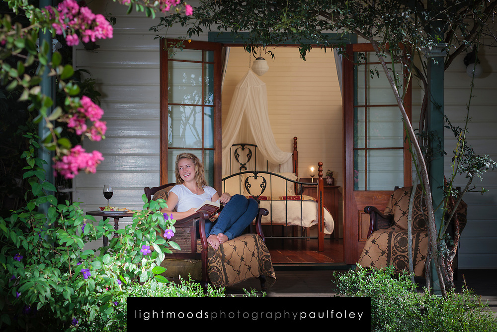 Young woman reading on the verandah of a bed and breakfast, Maitland, Australia