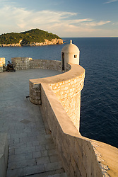 Europe, Croatia, Dalmatia, Dubrovnik.  Old city walls (built 10th century) above Adriatic Sea.  Lokrum Island is beyond. The historic center of Dubrovnik is a UNESCO World Heritage site.