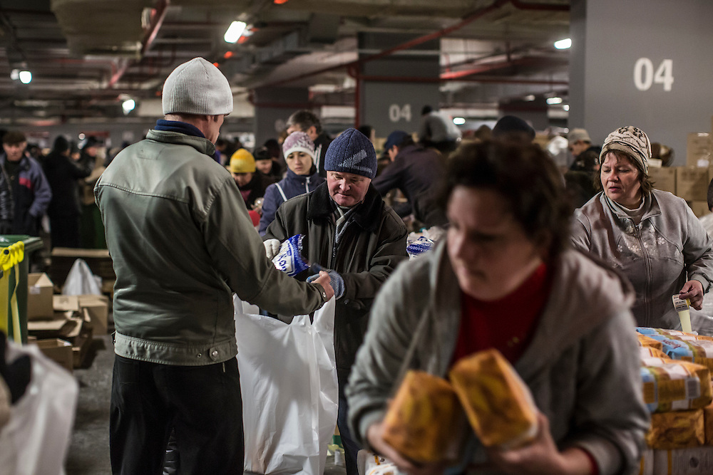 DONETSK, UKRAINE - JANUARY 26, 2015: Food and other supplies are distributed to residents in need at the Donbass Arena soccer stadium in Donetsk, Ukraine. With many residents finding it difficult to access bank accounts or find work, humanitarian needs are rising. CREDIT: Brendan Hoffman for The New York Times