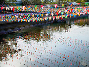 31 MARCH 2015 - BANGKOK, THAILAND: Decorative flags hanging over Khlong Krung Kasem are reflected in the surface of the Khlong (canal) in Bangkok.     PHOTO BY JACK KURTZ