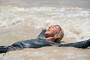 Woman laying on the edge of water on a beach in the Galapagos Islands, Ecuador.