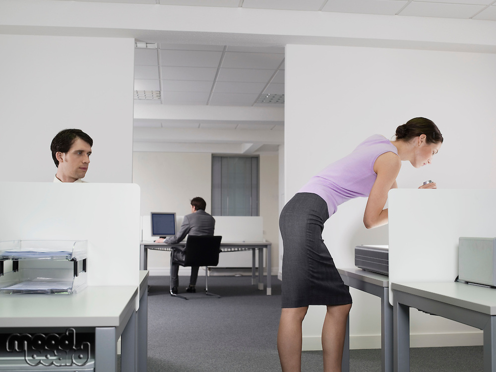Businessman watching female colleague in office
