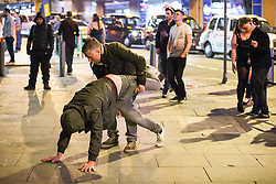 © Licensed to London News Pictures . Manchester , UK . 05/04/2015 . A man grabs another man by the legs as the two dance on the pavement on Withy Grove in Manchester City Centre . Revellers on a Saturday night out during the Easter Bank Holiday weekend . Photo credit : Joel Goodman/LNP