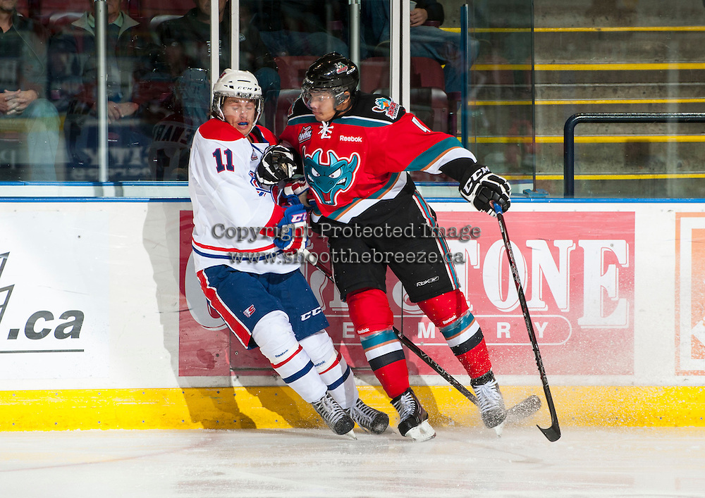 KELOWNA, CANADA - OCTOBER 10: Madison Bowey #4 of the Kelowna Rockets checks Liam Stewart #11 of the Spokane Chiefs into the boards as the Spokane Chiefs visit the Kelowna Rockets on October 10, 2012 at Prospera Place in Kelowna, British Columbia, Canada (Photo by Marissa Baecker/Shoot the Breeze) *** Local Caption ***