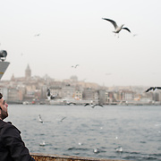A man feeds the seagulls at the Eminonu waterfront in Istanbul, with the Galata Tower in the background left.
