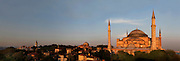 Panoramic view of Hagia Sophia, 532-37, by Isidore of Miletus and Anthemius of Tralles, with the Topkapi Palace on the left, Istanbul, Turkey. Hagia Sophia, The Church of the Holy Wisdom, has been a  Byzantine church and an Ottoman mosque and is now a museum. The current building, the third on the site, commissioned by Emperor Justinian I, is a very fine example of Byzantine architecture. The historical areas of the city were declared a UNESCO World Heritage Site in 1985. Picture by Manuel Cohen.