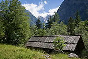 With the highest peaks in Slovenia in the distance is a traditional Slovenian mountain hut in the Slovenian Julian Alps, on 22nd June 2018, in Trenta, Triglav National Park, Slovenia. Beyond are the mountains, Kreiski 2050m, Pihavec 2419m, Dolina Zadnjica and Triglav 2864m.