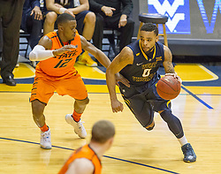 West Virginia Mountaineers guard Jaysean Paige (0) tries to drive past Oklahoma State Cowboys guard Anthony Hickey Jr. (12) during the second half at the WVU Coliseum.