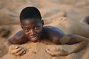 After some boys run and leap into the Niger River in the late afternoon at the W. African village of Kouakourou, Mali, one of them lies in the warm sand on the river's edge. Material World Project.