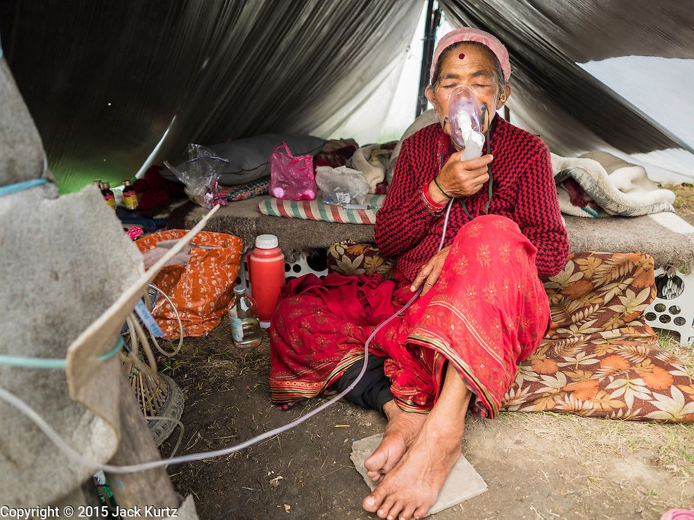 05 AUGUST 2015 - KATHMANDU, NEPAL: CHANDRA MAYA SUNAR, 57 years old, breathes through an oxygen mask in her tent in a large Internal Displaced Person (IDP) Camp in the center of Kathmandu. She came to Kathmandu with her family from Sindupalchok after the earthquake. The camp is next to one the most expensive international hotels in Kathmandu. More than 7,100 people displaced by the Nepal earthquake in April live in 1,800 tents spread across the space of three football fields. There is no electricity in the camp. International NGOs provide water and dug latrines on the edge of the camp but the domestic waste water, from people doing laundry or dishes, runs between the tents. Most of the ground in the camp is muddy from the running water and frequent rain. Most of the camp's residents come from the mountains in northern Nepal, 8 - 12 hours from Kathmandu. The residents don't get rations or food assistance so every day many of them walk the streets of Kathmandu looking for day work.     PHOTO BY JACK KURTZ