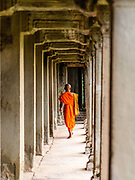 Monk walking along an outdoor hallway.  Angkor Wat Temple; Angkor Wat Archeological Park, Siem Reap, Cambodia.