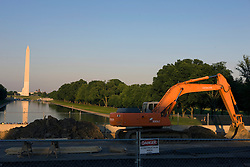 An orange Hitachi excavator sits on a side walk construction zone between the Washington Monument pictured in the background and the the Lincoln Memorial, National Mall and Memorial Parks, Washington, DC - June 3, 2008