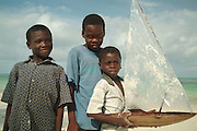 Africa. Tanzania. Zanzibar. Jambiani Beach..Young boys with model boat made from palm leaves..CD0010