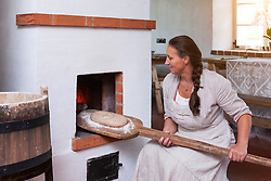 Woman at stove in Hellenurme watermill, Estonia. Preparing, bread on baker`s shovel. Rural interior.