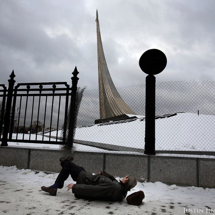 A man wearing a fur hat slips as he walks on ice in front of a rocket momument in Moscow. The momument was built during Soviet times to commemorate its space achievement. ..Picture by Justin Jin.