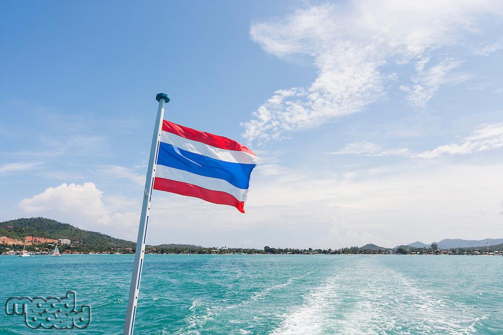 Thailand flag with boat wake at Koh Pha Ngan island