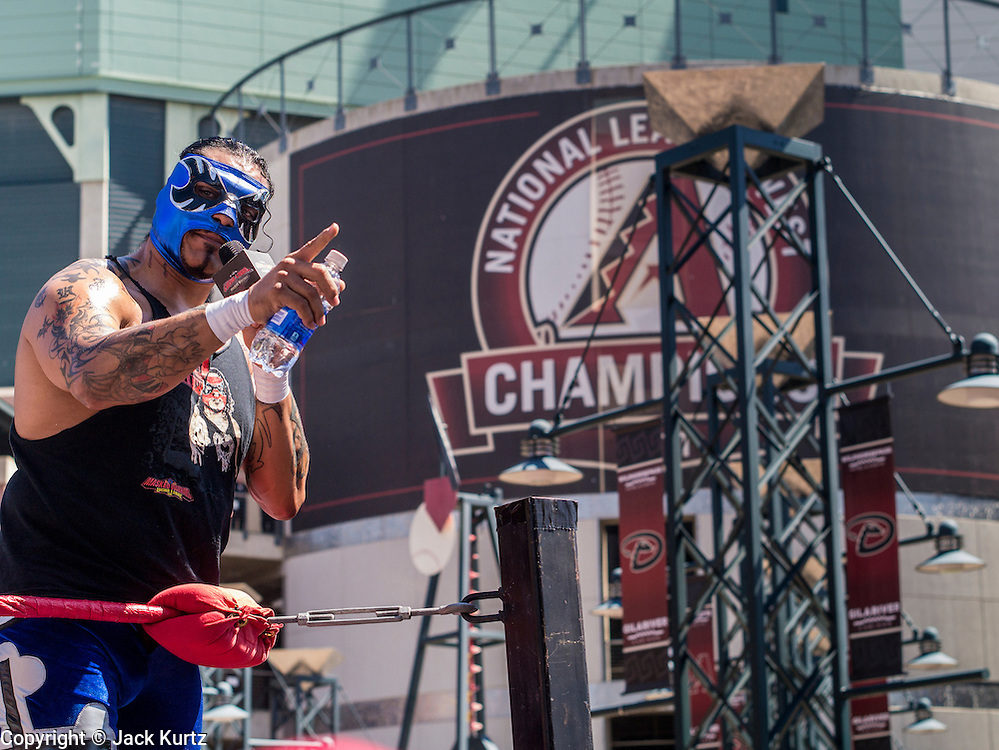 """16 SEPTEMBER 2012 - PHOENIX, AZ:  LIZMARK JR., a Lucha Libre wrestler from Acapulco, Mexico, talks to the crowd before a Lucha Libre mask in front of Chase Field on Hispanic Heritage Day. He is a Lucha Libre """"Rudo"""" or villain. The Arizona Diamondbacks hosted their 14th Annual Hispanic Heritage Day, Sunday to kick off Hispanic Heritage Month (Sept. 15-Oct. 15) before the 1:10 p.m. game between the D-backs and San Francisco Giants. The main attraction of the Day was three Lucha Libre USA exhibition wrestling matches in front of Chase Field stadium before the game. PHOTO BY JACK KURTZ"""