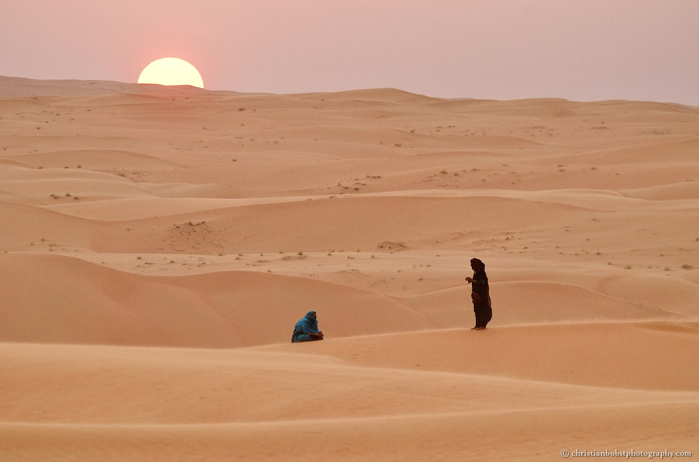 Beduin women praying at sunset in the desert in Wahiba Sands, Oman, 2011