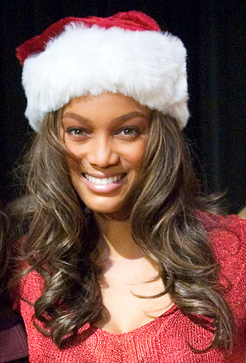 Television personality TYRA BANKS smiles wearing a red santa christmas hat after giving out presents to high school students at Redondo Union High School in Redondo Beach, Calif. on Dec. 5, 2005.