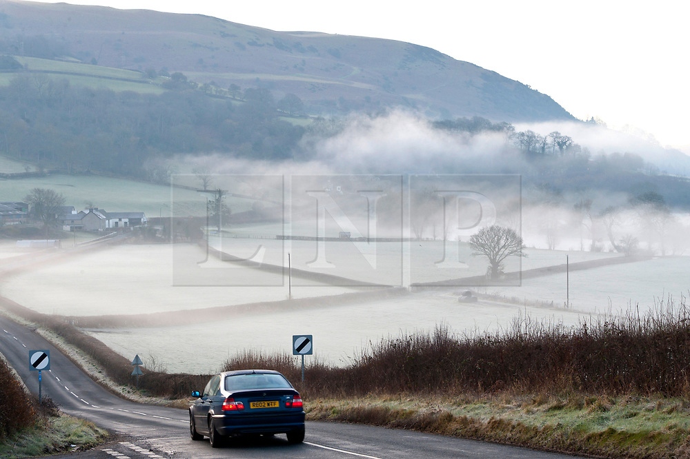 © Licensed to London News Pictures. 14/02/2019. Builth Wells, Powys, Wales, UK. A motorist drives along a rural road through a wintry landscape near Builth Wells in Powys. Frost and mist are seen in the Wye Valley near Builth Wells in Powys, Wales UK after temperatures drop to below zero degrees centigrade overnight. Photo credit: Graham M. Lawrence/LNP