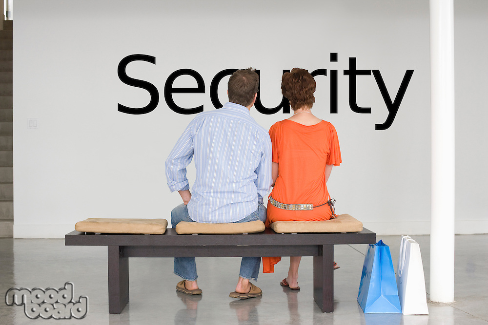 Rear view of couple seated on bench contemplating about future security