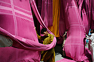 As they hang in the sun and blow in the breeze Afzal Muhammad, center, works to to untangle and fold the huge sheets of fabric that will be cut into towels at the A-One Textile & Towel Industries in Karachi, Pakistan and readied for delivery to mail-order catalogs and resorts in the U.S.