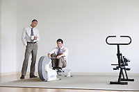 Business man using rowing machine colleague standing by