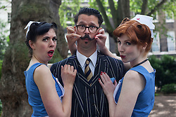 © licensed to London News Pictures. London, UK 08/07/2012. Two vintage nurse lookalikes posing with a man at the Chap Olympiad in Bedford Square Gardens in central London today. Photo credit: Tolga Akmen/LNP