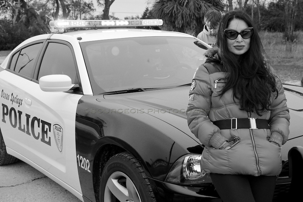 Saye Yabandeh leans up against a police car on the set of her action movie releasing in 2013, Blunt Force.