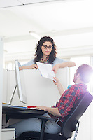 Businessman handing over document to female colleague over cubicle wall