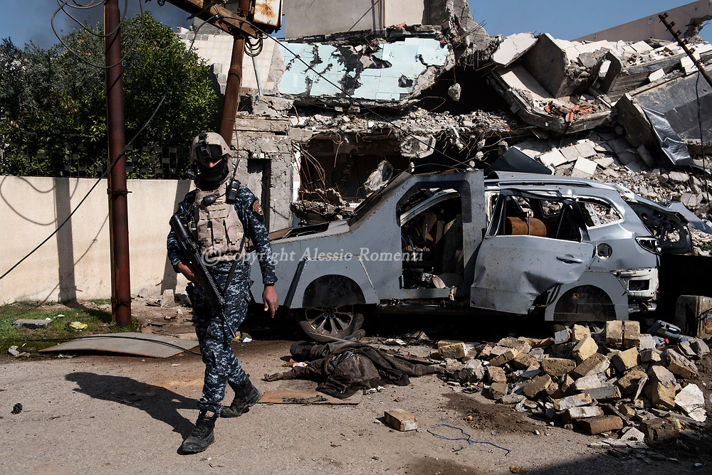 Iraq, Mosul: An Iraqi soldier walks near by the body of an alleged Islamic State militant and a damaged car bomb in a neighbourhood recently secured by Iraqi security forces in western Mosul. Alessio Romenzi