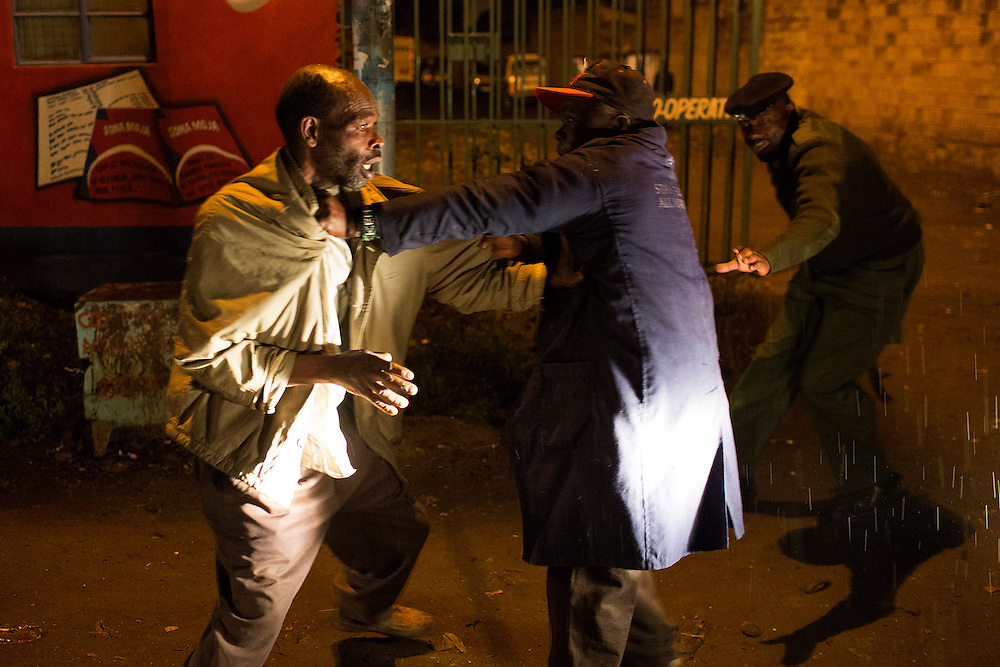 A police officer intervenes to stop two men fighting on a street in the slum of Korogocho during a night patrol in Nairobi.